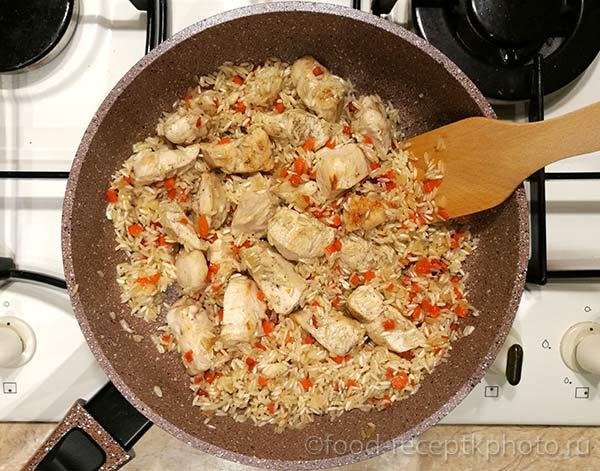 Лук,филе ,рис и морковь в сковороде для приготовления плова с курицей