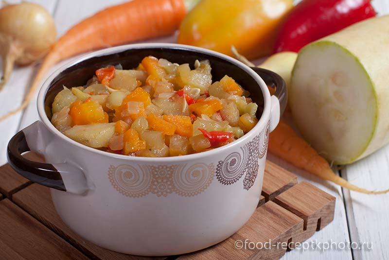 Овощное рагу в кастрюле для запекания на фоне овощей