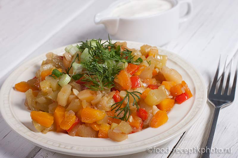 Овощное рагу в белой тарелке и соусник со сметаной на белом столе