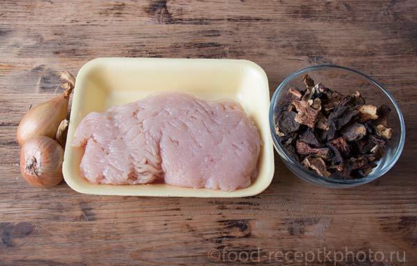 Куриный фарш. лук и сухие грибы на деревянном столе