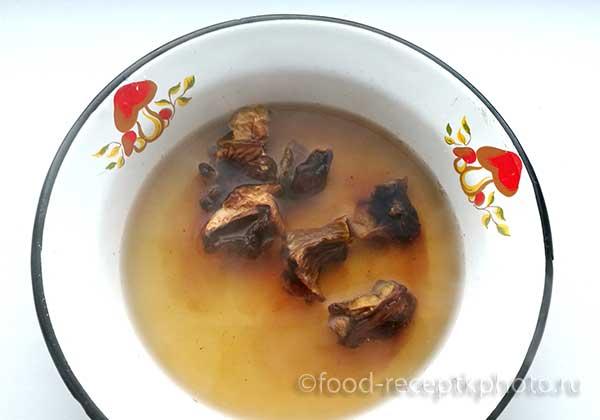 Сухие грибы в миске с водой