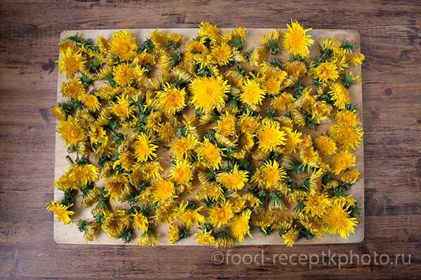 Цветки одуванчиков на деревянной доске для просушки