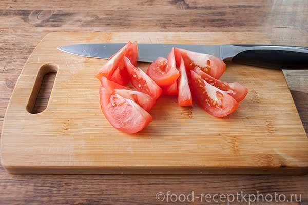На разделочной доске нарезанные помидоры
