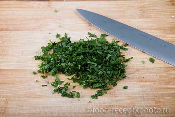 Нарезанная зелень петрушки на разделочной доске